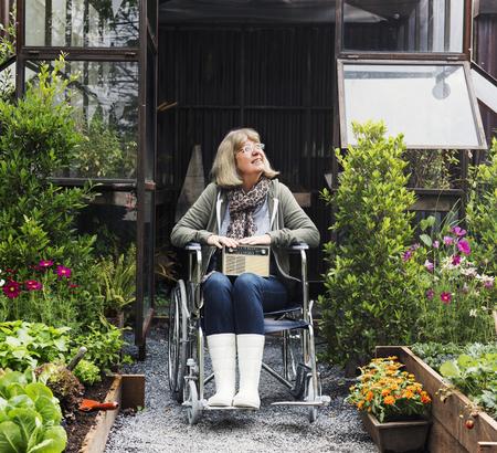 Senior adult woman on wheelchair in the garden Stock fotó