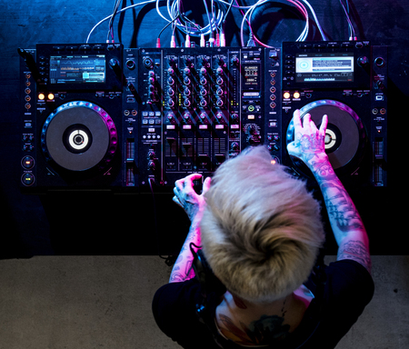 Dj playing music at sound mixer in night club Stock Photo