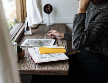 태블릿 및 노트북으로 책상에 앉아있는 사람