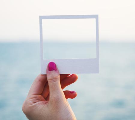 海の背景を持つ穿開いたペーパーフレームを手に保持 写真素材