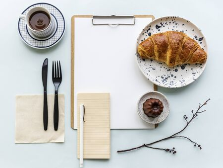 Aerial view of croissant coffee cup and paper clipboard