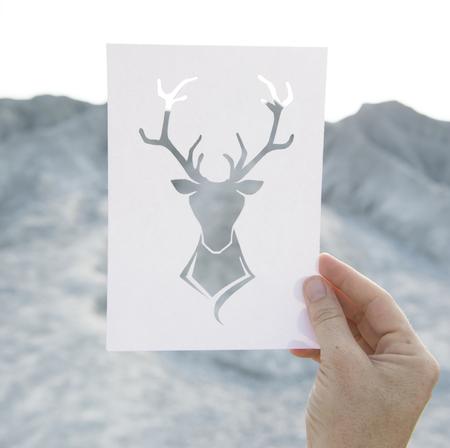 Hand die geperforeerde document Amerikaanse elandenkunst met bergachtergrond houden Stockfoto