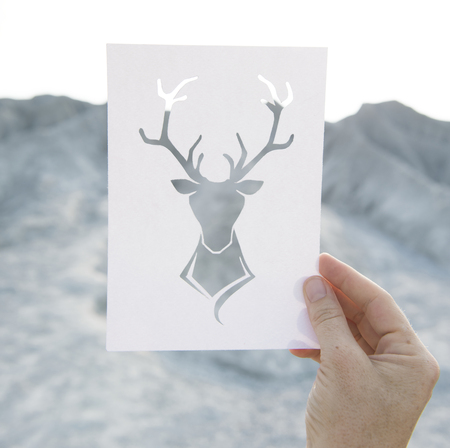 Hand holding perforated paper moose art with mountain background Imagens