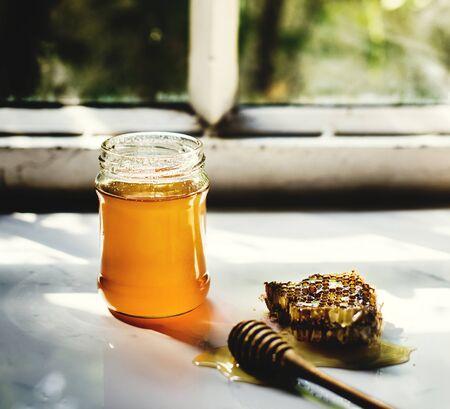 Close-up van honingraat met dipper op marmeren lijst Stockfoto