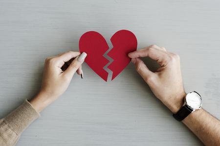 Hands holding a broken paper heart