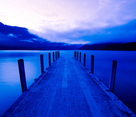 Boat jetty and a calm lake at sunrise, New Zealand.