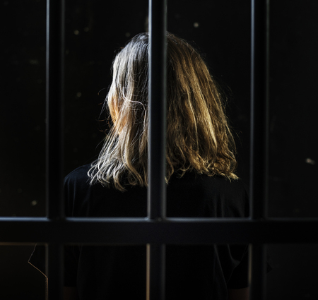 Back view of a woman behind bars