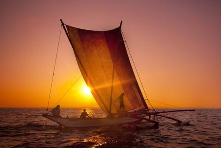 Fishermen on a catamaran at Sunset. Sri Lanka Stock Photo