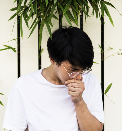 Guy coughing sneezing covering mouth