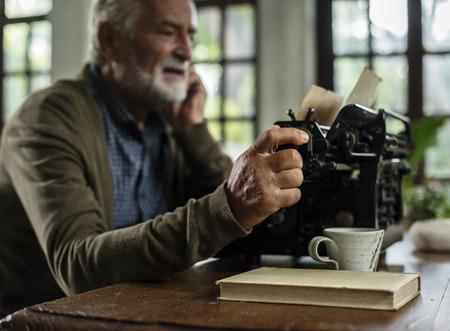 Senior caucasian man using vintage typewriter