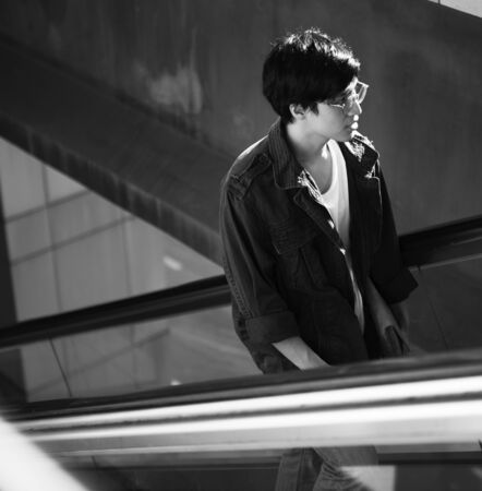 Handsome asian guy on the escalator