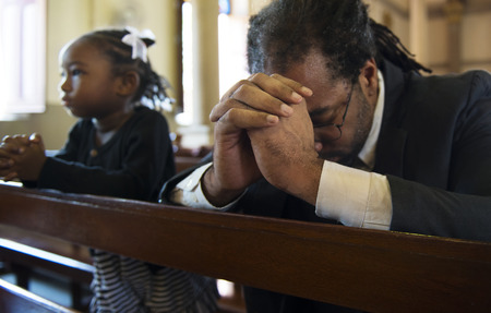 Religious man praying inside a church