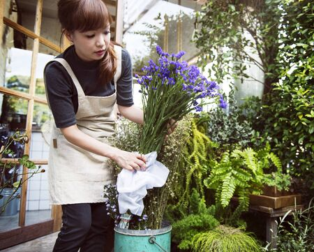 Woman arranging flowers in her shop Stok Fotoğraf - 90758316