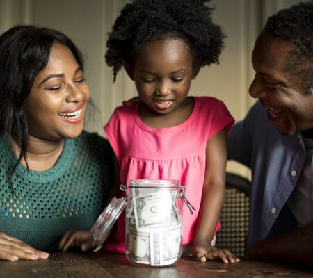 Parents teaching their daughter on how to save money