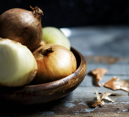 Closeup of fresh onions in wooden bowl