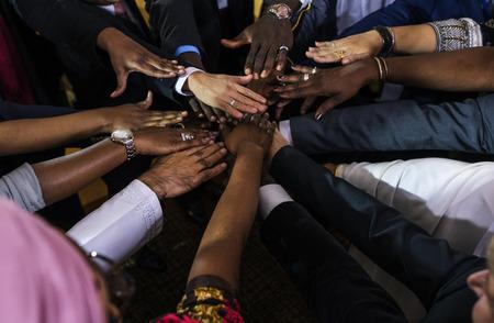 Een groep internationale zakenmensen steken hun handen in elkaar