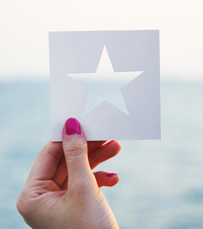 海の背景を持つ穿開かれた紙の星の形を手に保持 写真素材