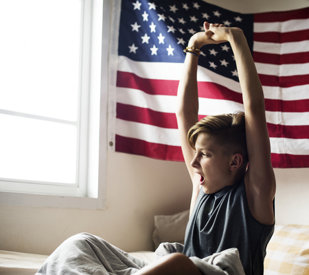 Young caucasian boy waking up stretching arms Imagens