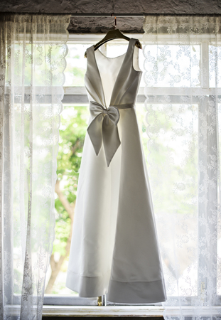 White Wedding Dress Hanging by the Window Reklamní fotografie - 90762988