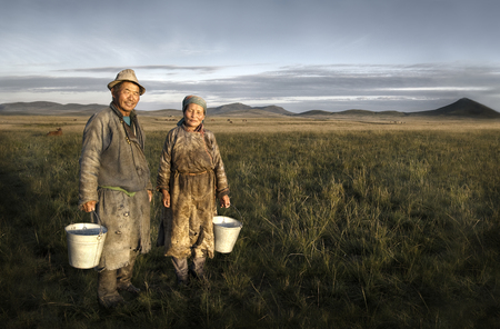 Mongolian couple farmers holding basin and posing in the field. Banco de Imagens