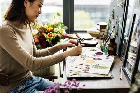 Woman writing as she creates floral project