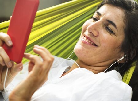 An Adult Woman Using Mobile Phone on a Hammock
