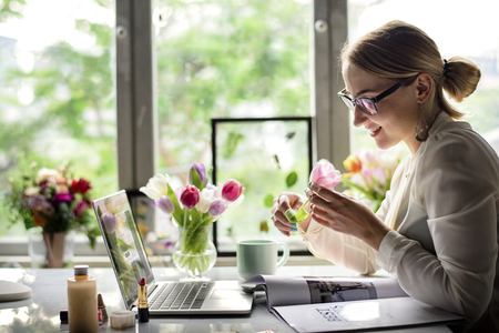 Woman smelling a flower in the office  Banque d'images