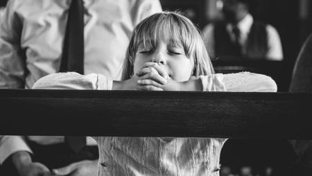A child praying inside the church Stock Photo
