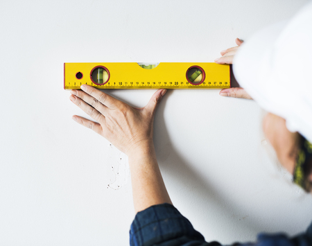 Repairman working with measuring ruller on the wall