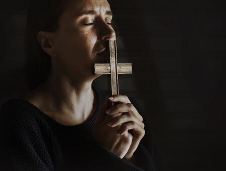 Incrocio della tenuta della donna che prega per Dio Archivio Fotografico - 90761147
