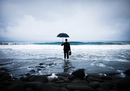 Businessman with an umbrella on the beach Stock Photo