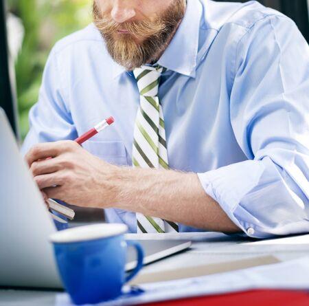 Bearded businessman taking notes Stock Photo