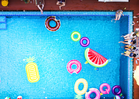 Luchtfoto van mensen genieten van het zwembad met kleurrijke opblaasbare drijvers