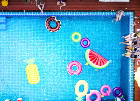 Vista aérea de personas disfrutando de la piscina con coloridos flotadores inflables
