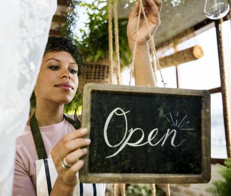 Vrouw die Open Teken bij het Glasvenster hangt Stockfoto