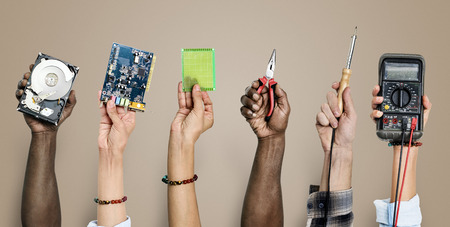 Diverse hands holding electronics tools on brown background