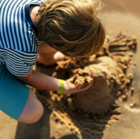 Little boy playing sand by the seashore Stock Photo