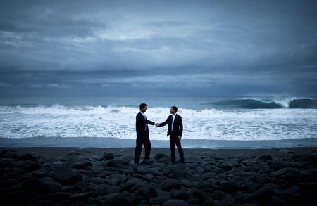 Business handshake on the beach.