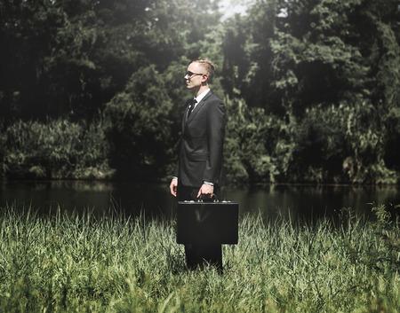 Homem de negócios de pé em uma pastagem