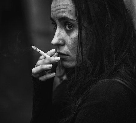 Woman smoking cigarette alone grayscale