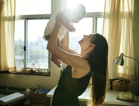 Mutter, die ihr Baby mit Liebe hochhält