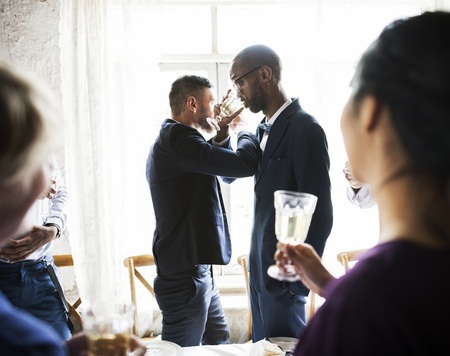 Gay Couple Arms Crossed Drinking Champagne Together Standard-Bild