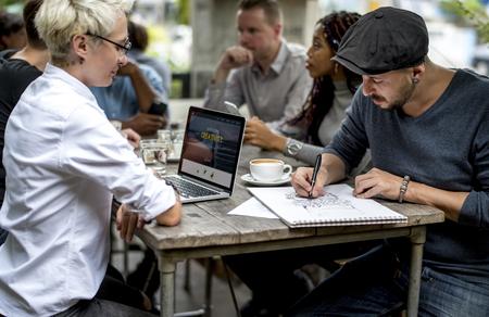 Frauen-Gebrauch-Laptop sitzen mit Freunden