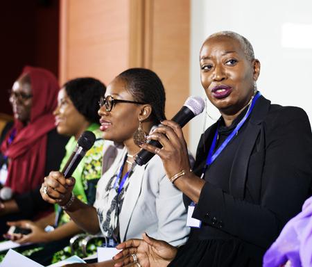 Uma mulher do meio-africano que fala em um microfone Imagens