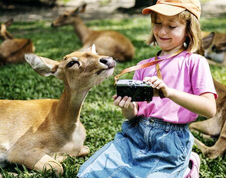 Rapaz caucasiana que leva selfie com deers no zoológico