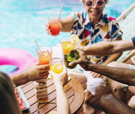 Groupe d'adultes senior divers bénéficiant de boisson au bord de la piscine ensemble Banque d'images