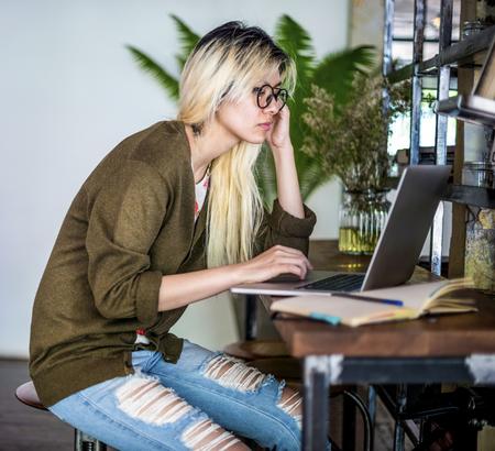 Blonde asiatische Frau, die an einem Laptop arbeitet Standard-Bild
