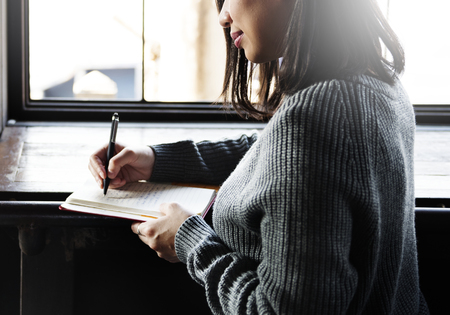 Asian woman writing on a notebook Imagens
