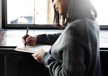 Femme asiatique écrit sur un cahier Banque d'images