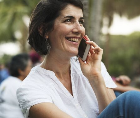 An Adult Woman Talking on The Phone in the Park